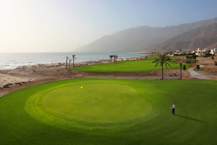 Jebel Sifah 7th green against a stunning backdrop of mountain terrain and seafront