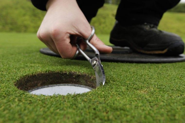 cutting the grass around the hole 59Club